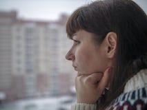 De jonge vrij donkerbruine vrouw met lang haar kijkt zorgvuldig terwijl status bij het vensterclose-up royalty-vrije stock afbeeldingen