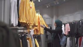 De jonge vrij moslimvrouw in een hijab en met een rugzak kiest kleren in de opslag stock video