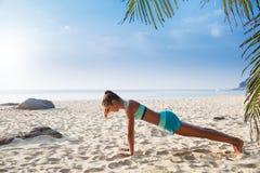 De jonge vrij slanke donkerbruine yoga van de vrouwenpraktijk stelt op tropisch Stock Afbeelding