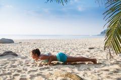 De jonge vrij slanke donkerbruine yoga van de vrouwenpraktijk stelt op tropisch Stock Fotografie