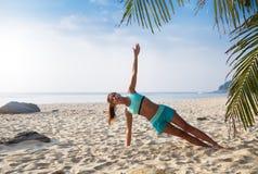 De jonge vrij slanke donkerbruine yoga van de vrouwenpraktijk stelt op tropisch Royalty-vrije Stock Afbeelding