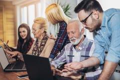 De jonge vrijwilligers helpen hogere mensen op de computer royalty-vrije stock foto's