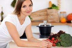 De jonge vrolijke glimlachende vrouw is klaar voor het koken in een keuken Huisvrouwenzitting bij de lijst en het bekijken de cam Stock Fotografie