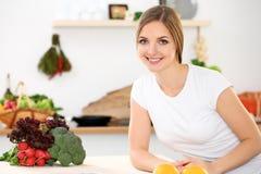 De jonge vrolijke glimlachende vrouw is klaar voor het koken in een keuken Huisvrouwenzitting bij de lijst en het bekijken de cam Stock Foto