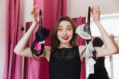 De jonge vrolijke lingerie van de vrouwenholding Stock Foto