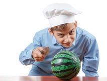 De jonge vrolijke tiener guffaw, lacht luid en humeur in de hoed van een chef-kok Geïsoleerde studio stock fotografie