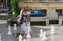 De jonge vrolijke vrouw houdt groot schaakstuk op straat in oude stad Stock Afbeelding