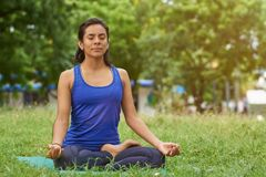 De jonge vrouw ademhaling in yoga stelt stock foto's