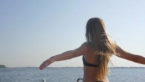 De jonge vrouw in badpak geniet van van vrijheid en omhoog het Opheffen van Handen op overzees in Zomer, Luxueus haar die binnen  stock footage