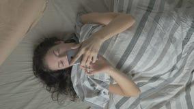 De jonge vrouw in bed ontwaakt in de ochtend en op de telefoon De mening vanaf de bovenkant stock videobeelden