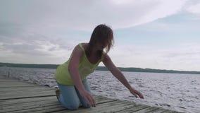 De jonge vrouw begint steun op oude houten pijler te leunen stock videobeelden