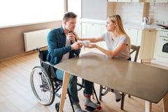 De jonge vrouw behandelt de mens met speciale behoeften Hij zit op rolstoel en krijgt kop van hete drank Ziek en ziek Mens die me stock foto