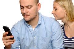 De jonge vrouw bekijkt de telefoon van haar echtgenoot. Stock Fotografie