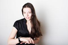 De jonge vrouw bekijkt haar polshorloge Het concept van het tijdbeheer, altijd op tijd stock foto