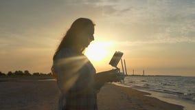 De jonge vrouw bekijkt omhoog met een vliegend hommelpaneel zonsondergang in slo-mo stock videobeelden