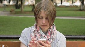 De jonge vrouw bekijkt de telefoon in het stadspark, Georgië stock video