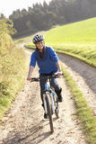 De jonge vrouw berijdt haar fiets in park Stock Afbeelding
