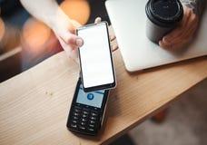 De jonge vrouw betaalt via betaling eind en mobiele telefoon in koffie stock foto