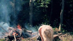 De jonge vrouw beweegt zich actief tegen de achtergrond van de heldere brand stock video