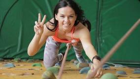 De jonge vrouw is bij het beklimmen van muur in onbeweeglijke staat in sportclub stock footage