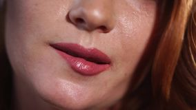 De jonge vrouw bijt coquettishly haar lippen en helt haar hoofd over stock videobeelden