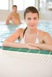 De jonge vrouw in bikini ontspant in zwembad Stock Afbeeldingen