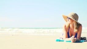 De jonge vrouw in blauwe bikini ligt op het strand met een uitstekende camera en heeft een zonhoed stock footage