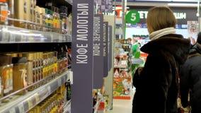 De jonge vrouw in bontjas kiest koffiepunt in supermarkt stock video