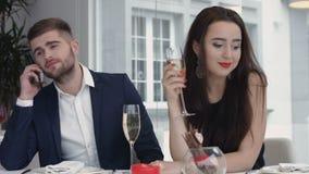 De jonge vrouw bored tot op heden terwijl haar vriend die commerciële cel op mobiele telefoon, man hebben bezig het gebruiken van Royalty-vrije Stock Fotografie