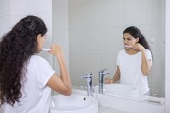 De jonge vrouw borstelt tanden in de badkamers stock foto's