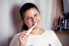 De jonge vrouw borstelt tanden in badkamers een elektrische borstel Stock Fotografie