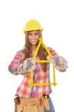 De jonge vrouw bouwt huis van een vouwmeter Stock Afbeelding