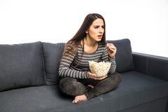 De jonge vrouw brengt zijn vrije tijd lettend op TV aan de laag door smakkend spaanders en popcorn witte achtergrond Stock Afbeelding