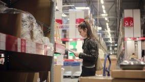 De jonge vrouw controleert haar lijst, neemt een gootsteen en pijpen van een plank en zet hen op het karretje in een pakhuis stock videobeelden