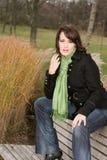 De jonge vrouw in de herfst zit op een bank Royalty-vrije Stock Afbeelding