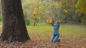 De jonge vrouw in de herfstpark werpt op een armvol esdoornbladeren stock footage