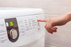 De jonge vrouw of de huishoudster hebben een wasserijdag thuis, selecteert zij het programma stock foto