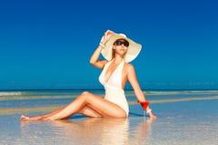 De jonge vrouw in de zitting van de strohoed bij het tropische strand en geniet van Royalty-vrije Stock Foto's