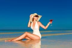 De jonge vrouw in de zitting van de strohoed bij het tropische strand en geniet van Royalty-vrije Stock Foto