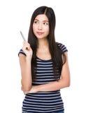 De jonge vrouw denkt aan het idee met het houden van een pen Royalty-vrije Stock Foto