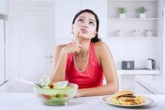 De jonge vrouw denkt om hamburger of salade te kiezen stock foto