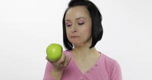 De jonge vrouw die appel eten en zegt yum Het meisje neemt eerste beet en zegt behoefte aan beet stock videobeelden