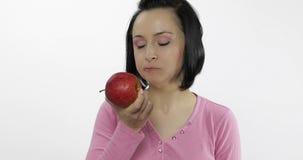 De jonge vrouw die appel eten en zegt yum Het meisje neemt eerste beet en zegt behoefte aan beet stock video