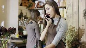 De jonge vrouw, die in bloemwinkel werkt, talkes een orde door de telefoon en de nota's het in noterbook, camera gaat van bodem stock videobeelden