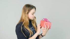 De jonge vrouw die een gift bekijken en wil weten welke ` s binnen op witte achtergrond stock fotografie