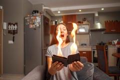 De jonge vrouw die een portefeuille, portefeuille op brand, verrast meisje, magische conceptennadruk, portefeuille houden brandt  stock fotografie