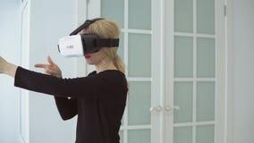 De jonge vrouw die ervaring krijgen die VR-hoofdtelefoonglazen van virtuele werkelijkheid gebruiken thuis veel het gesticuleren o stock video