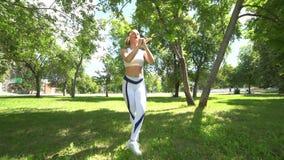 De jonge vrouw die geschiktheid doen oefent in openlucht uit Geschikt meisje die in park springen Training en geschiktheid in bos stock video