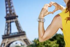 De jonge vrouw die gevormd hart tonen dient Parijs, Frankrijk in royalty-vrije stock fotografie