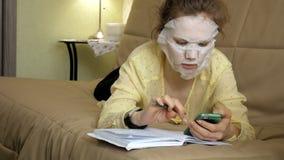 De jonge vrouw die gezichtsmaskermasker met het reinigen van masker doen, klikt thuis op laag met smartphone stock foto's